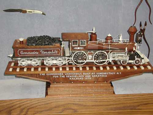 Picture of The Commodore Vanderbilt <br>one of the trains Mr. Warther carved. <br>Also, a knife and tools can be seen in the background.