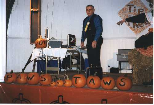 Stage display of pumpkins spelling out Paws and Taws with caller in background.
